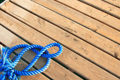Nautical Background. Blue boat rope on a wooden dock Royalty Free Stock Images