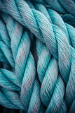 Nautical background. Closeup of an old blue frayed boat rope. Tonned image Stock Images