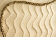 Nautical background of wavy sand with a rope Stock Images