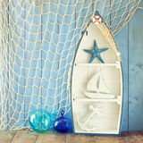 Nautical boat shape shelves and nautical life style objects on wooden table. vintage filtered.  Royalty Free Stock Images