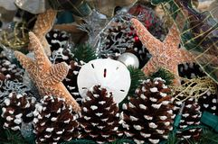 Nautical Christmas Decorations. Photographed at a local outdoor market in Florida. Like the idea of starfishn and sanddollar mixed in with the pine cones Stock Photo