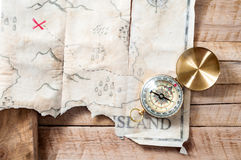 Nautical compass with fake treasure map of abstract island with red cross on wooden table Stock Photos