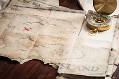Nautical compass on treasure map of abstract island on wooden table Royalty Free Stock Photography