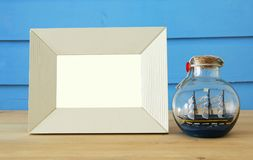 Nautical concept with empty photo frame and sail boat in the bottle over wooden table. For photography montage. Nautical concept with empty photo frame and sail stock images