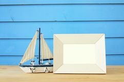 Nautical concept with empty photo frame and sail boat over wooden table. For photography montage. Nautical concept with empty photo frame and sail boat over stock photo