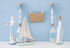 Nautical concept with hanging empty note on a string next to boat, letter in the bottle and seagull over blue background. Nautical concept with hanging empty Stock Photo