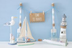 Nautical concept with hanging note on a string next to lighthouse, boat, letter in the bottle and seagull over blue background. Nautical concept with hanging Royalty Free Stock Images