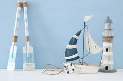Nautical concept image with decorative oars, boat and lighthouse over light blue background. Nautical concept image with decorative oars, boat and lighthouse Royalty Free Stock Photos