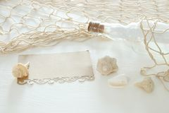 Nautical concept image with letter in the bottle, seashells, fish net and empty note over white wooden table. Nautical concept image with letter in the bottle Stock Photos
