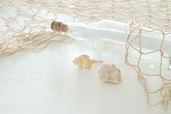 Nautical concept image with letter in the bottle, seashells and fish net over white wooden table. Nautical concept image with letter in the bottle, seashells Royalty Free Stock Photos