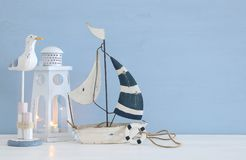Nautical concept image with white decorative seagull bird, boat and lighthouse lantern over light blue background. Nautical concept image with white decorative Stock Images