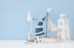 Nautical concept image with white decorative seagull bird, boat and lighthouse lantern over light blue background. Nautical concept image with white decorative Royalty Free Stock Photo