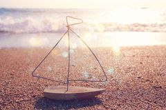 Nautical concept with sail boat infront of sunset sea and beach landscape royalty free stock images