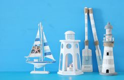 Nautical concept with white decorative lantern, lighthous, wooden oars and boat oars over blue background. Nautical concept with white decorative lantern Stock Photos