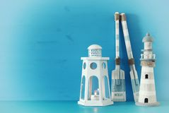 Nautical concept with white decorative lantern, lighthouse and wooden boat oars over blue background. Nautical concept with white decorative lantern, lighthouse Stock Photography