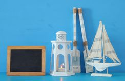 Nautical concept with white decorative lighthouse lantern, woode. N oars and boat next to empty blackboard over blue background Stock Images