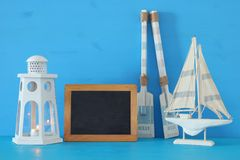 Nautical concept with white decorative lighthouse lantern, wooden oars and boat next to empty blackboard over blue background. Nautical concept with white Royalty Free Stock Photos