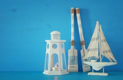 Nautical concept with white decorative lighthouse lantern, wooden oars and boat over blue background. Nautical concept with white decorative lighthouse lantern Stock Image