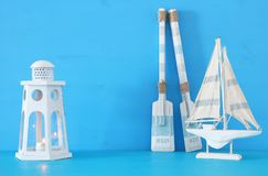 Nautical concept with white decorative lighthouse lantern, wooden oars and boat over blue background. Nautical concept with white decorative lighthouse lantern Stock Photos