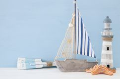 Nautical concept with white decorative lighthouse, wooden oars and boat over blue background. Nautical concept with white decorative lighthouse, wooden oars and Stock Photography