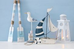 Nautical concept with white decorative seagull bird, lighthous lantern, wooden oars and boat over blue background. Nautical concept with white decorative Stock Images