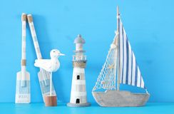 Nautical concept with white decorative seagull bird, lighthous, wooden oars and boat oars over blue background. Nautical concept with white decorative seagull Royalty Free Stock Images