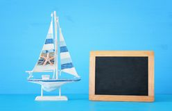 Nautical concept with white decorative wooden boat next to empty blackboard for copy space over blue background. Nautical concept with white decorative wooden Royalty Free Stock Image