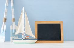 Nautical concept with white decorative wooden oars and boat next to empty blackboard over blue background. Nautical concept with white decorative wooden oars Stock Images