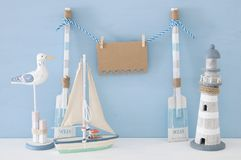 Nautical concept with wooden decorative boat oars and empty hanging note on a string next to lighthouse, seagull and boat over blu. E background Stock Image