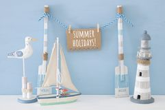 Nautical concept with wooden decorative boat oars and hanging note message on a string next to lighthouse, seagull and boat over b. Lue background Stock Photos