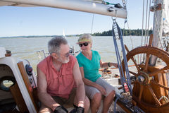 Nautical Discussion. A retired couple on their sailboat converse as they sail on an Oregon lake stock photo