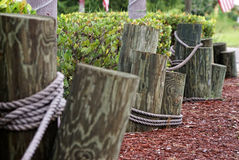 Nautical fencing. Wooden poles are mounted in the ground and tied together with rope making for a nautical type fencing or boundary on an overcast day Royalty Free Stock Photo