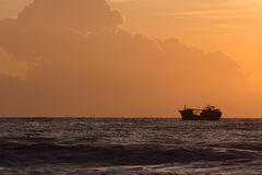 Nautical fishing boat in sea with beautiful sky sunrise Stock Images