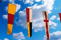 Nautical Flags on a Blue Sky (098). Three nautical flags hanging from a rope on a blue sky with clouds - representing the numbers 0, 9, 8 Royalty Free Stock Image