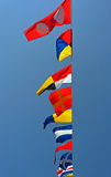 Nautical Flags. A row of nautical flags fly in the wind against a blue sky Stock Photography