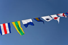 Nautical Flags. A row of nautical flags fly in the wind on a beautiful blue sky day Stock Photos
