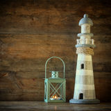 Nautical lifestyle concept. old vintage lighthouse and lantern on wooden table. vintage filtered image   Stock Image