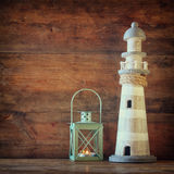 Nautical lifestyle concept. old vintage lighthouse and lantern on wooden table. vintage filtered image.  Stock Photography