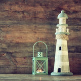 Nautical lifestyle concept. old vintage lighthouse and lantern on wooden table. vintage filtered image Stock Photos