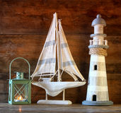 Nautical lifestyle concept. old vintage lighthouse, sailing boat and lantern. On wooden table. vintage filtered image Royalty Free Stock Photo