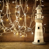 Nautical lifestyle concept. old vintage lighthouse on wooden table and warm gold garland lights. vintage filtered image Stock Photography
