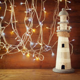 Nautical lifestyle concept. old vintage lighthouse on wooden table and warm gold garland lights. vintage filtered image Royalty Free Stock Photography