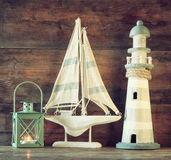 Nautical lifestyle evening concept. old vintage lighthouse, sailing boat and lantern on wooden table. vintage filtered image.  Royalty Free Stock Photo