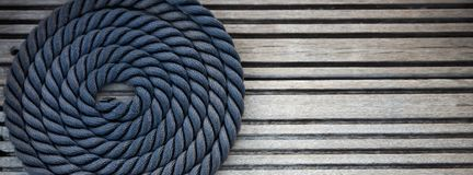 Nautical mooring rope. A curled mooring rope on a wooden pier. Copy space. Long wide banner stock photography