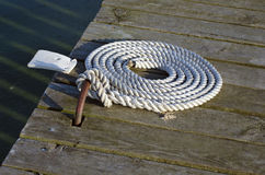 Nautical mooring rope on wooden pier. Mooring rope with  knotted end tied  on  wooden pier/ Nautical mooring rope Royalty Free Stock Photography