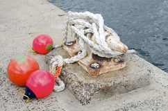 Nautical Mooring. Ropes with bright floats tied to a dockside cleat with nautical knots Royalty Free Stock Photos