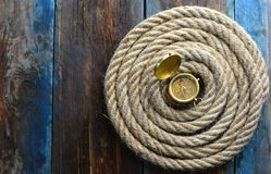 Nautical background. Old deck with rope and compass. Nautical navigation background. Old deck with rope and compass royalty free stock image