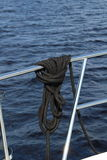 Nautical rope attached around a boat handrail. With water background Royalty Free Stock Image