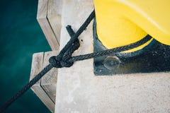 Nautical rope tied around a bollard. Mooring rope tied around a bollard on a pier royalty free stock photo