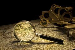 Nautical sextant and magnifying glass Royalty Free Stock Image
